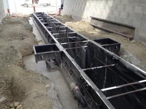 Dernier coulage béton autour de la fosse de garage préfabriquée en acier